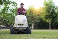 Gardener cutting the grass of a garde on a lawn mower Royalty Free Stock Photography