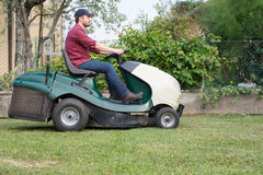 Gardener cutting the grass of a gardenon a lawn mower Stock Photography