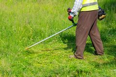 The gardener cutting grass by lawn mower, lawn care. Nature royalty free stock images