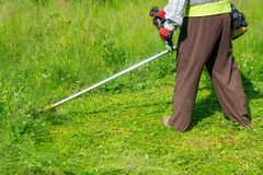 The gardener cutting grass by lawn mower, lawn care. Nature royalty free stock photography