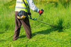 The gardener cutting grass by lawn mower, lawn care. Nature stock image