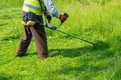 The gardener cutting grass by lawn mower, lawn care. Nature stock photos