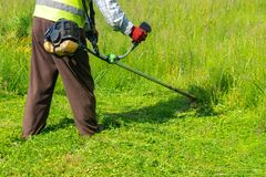 The gardener cutting grass by lawn mower, lawn care. Nature stock photo