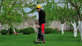 Gardener cutting grass with trimmer stock footage