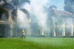 A gardener doing a poisoning activity by spraying insecticide or pesticides to control the insects in a hotel. fighting