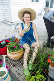 Gardener enjoying a refreshing iced drink. Attractive woman gardener wearing a straw sunhat sitting on her patio enjoying a refreshing iced drink as she takes a Royalty Free Stock Photo