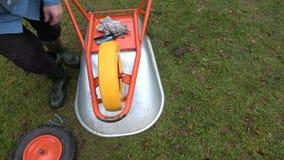 Gardener  fixing new wheelbarrow wheel. Gardener farmer  fixing new wheelbarrow wheel stock video footage