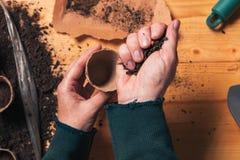 Gardener filling biodegradable soil pot container stock photo