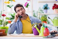 The gardener florist working in a flower shop with house plants. Gardener florist working in a flower shop with house plants Stock Photo