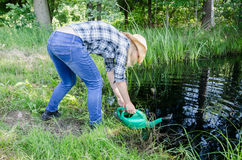 Gardener girl draw water from pond Royalty Free Stock Photos