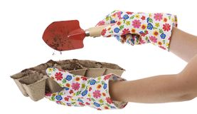 Gardener, Gloves, Shovel Putting Soil into Pots. Gardener wearing colorful flower patterned  gardening gloves is using a red shovel to place soil from a silver Royalty Free Stock Photos