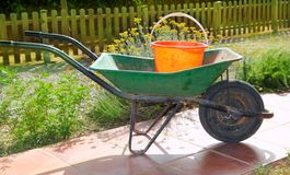 Gardener green wheel barrow with orange pail Royalty Free Stock Photos