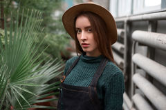 Gardener in hat and apron against green plants Stock Photos