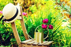 Gardener hat on wooden chair with watering can. In beautiful summer garden royalty free stock photos