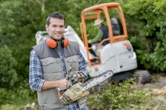 Gardener holding a chainsaw. Adults royalty free stock photos