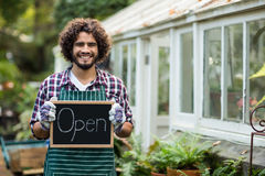 Gardener holding open sign placard outside greenhouse Royalty Free Stock Images