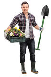 Gardener holding a shovel and crate with flowers Royalty Free Stock Photography