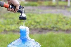 The gardener holds an irrigation sprinkler and collects clean water. The gardener holds an irrigation sprinkler and collects clean water in a blue bottle Stock Photos