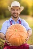 Gardener with huge pumpkin Royalty Free Stock Photo