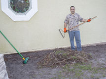 Gardener, Landscaper. A gardener, landscaper preparing ground for new landscaping - by a pile of ripped out grass, dirt and branches royalty free stock photography