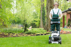 Gardener with the lawn mower Royalty Free Stock Photo