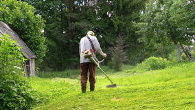 Gardener man cut grass with trimmer near rural house stock video footage