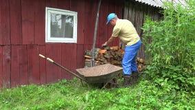 Gardener man unload firewood from wheelbarrow near wooden house. 4K stock footage
