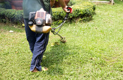 Gardener mowing the grass. With petrol weed trimmer Royalty Free Stock Photos