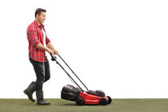 Gardener mowing a lawn with a lawnmower Royalty Free Stock Images