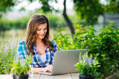 Gardener with notebook, sitting at the table, green nature Stock Image