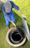 Gardener obove underground rainwater cistern Stock Photos