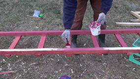 Gardener paint in red new wooden ladder stock video footage