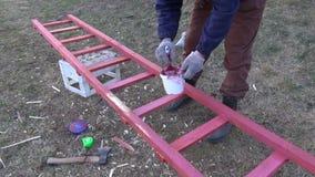 Gardener paint in red new wooden ladder stock video