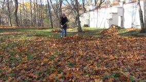 Gardener pile rake leaves stock footage
