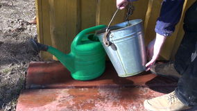 Gardener pouring water into green plastic watering can stock video