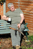 Gardener resting with a coffee. Royalty Free Stock Photo