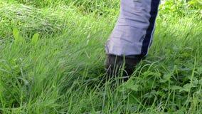 Gardener rubber waterproof boot shoe walk dew wet meadow grass stock footage