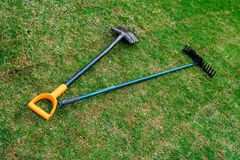 The gardener`s dirty shovel and rakes are lying on the fresh rolled lawn stock photos