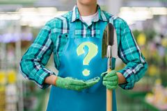 Gardener shows the question on blurred background. Royalty Free Stock Photo