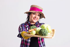 Gardener Shows a Vegetables on Tray. Long Hair Reliable Woman with Leghorn and Garden Gloves is Holding a Wicker Tray with Vegetables   Isolated on White Royalty Free Stock Image