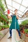 Gardener singing in water hose. Happy gardener singing in water hose in a greenhouse stock photos