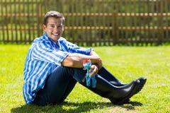 Gardener sitting on lawn Stock Image