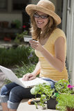 Gardener sitting outside using credit card and lap Stock Photography