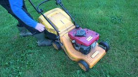 Gardener starting lawn mower  on grass stock video footage