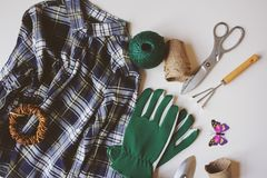 Gardener still life composition with spring preparations for yard work and transplanting. Plaid shirt, gloves, tools, peat pots on white background. Top view Stock Photos