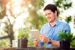 Gardener with tablet, sitting at the table, green nature. Gardener with tablet sitting at the table, managing supplies, green sunny nature Stock Photos