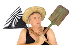 Gardener With Tools. Serious middle aged gardener with straw hat holds a rake and spade Royalty Free Stock Photo
