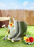 Gardener tools and equipment on a green lawn. Gardener tools and equipment like rubber boots, a watering can, pruning shears and a wicker basket on a green lawn Royalty Free Stock Photo