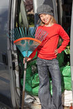 Gardener trainee kid. Smiling proud cute preteen blond handy girl as a gardener trainee or apprentice, standing in a gardening company van holding a rake Royalty Free Stock Image