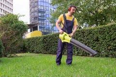 Gardener using his leaves blower garden stock photo
